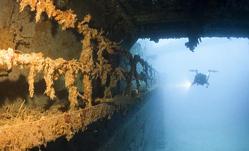 Diver-Lights-Up-Wreck-with-Flashlight