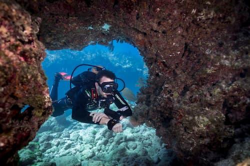SDI diver exploring coral with flashlight