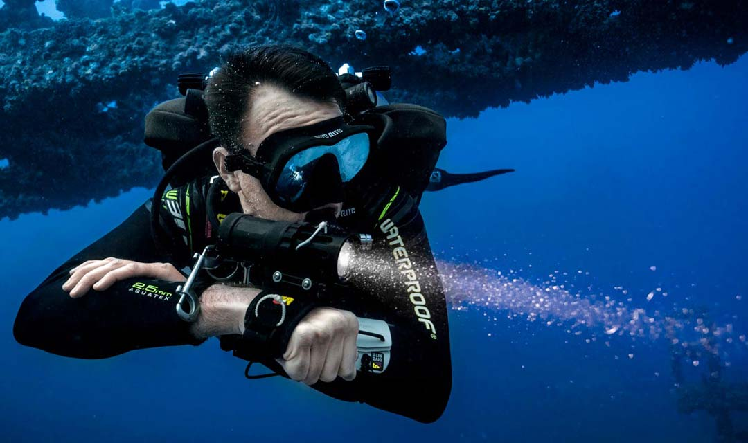 TDI-Diver-Points-Flashlight-with-Wreck-Behind-Him